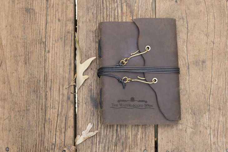 photo of a leather-bound journal on a wood background