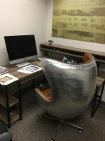 picture of a metal riveted chair by a desk