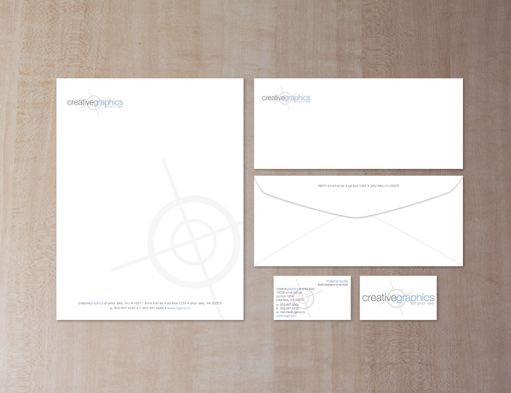 letterhead, business card (front and back), and envelope (front and back) on a light wood background