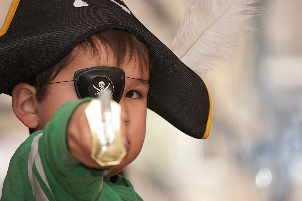 photograph of boy with sword, eye patch, and pirate hat with feather