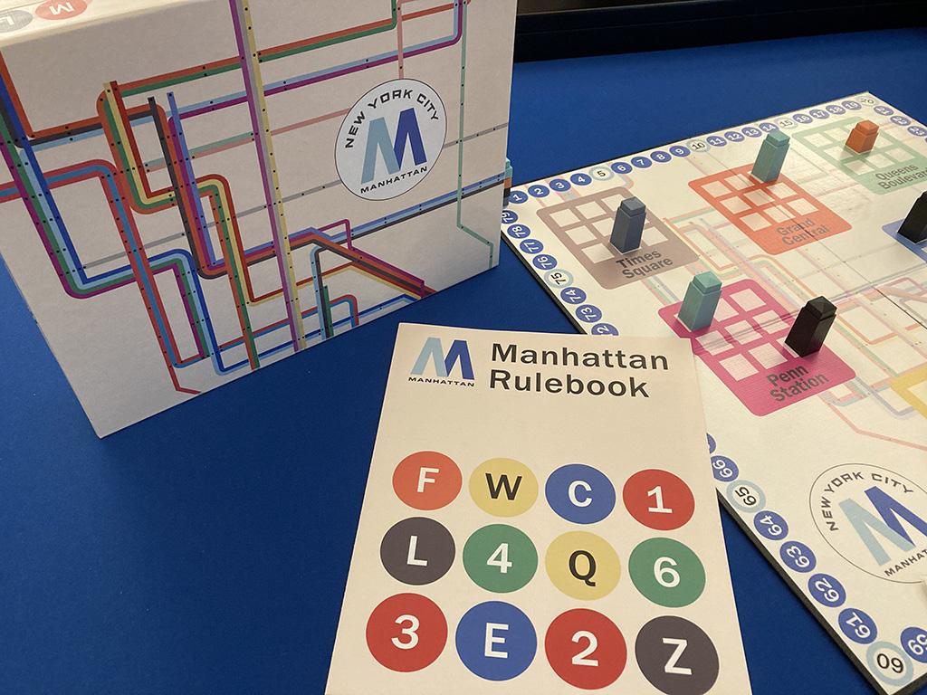 Closeup of Manhattan rulebook, box, and board